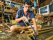 02 NOVEMBER 2016 - BANGKOK, THAILAND: KO, Gob's brother, saws teak for a spirit house. He works with his sister in the small family owned workshop that makes spirit houses by hand out of teak wood in the Ban Fuen community. There used to be 10 families making traditional spirit houses out of teak wood in Ban Fuen, a community near Wat Suttharam in the Khlong San district of Bangkok. The area has been gentrified and many of the spirit house makers have moved out, their traditional wooden Thai houses replaced by modern apartments. Now there is just one family making the elaborate spirit houses. The spirit houses are made by hand. It takes three days to make a small one and up to three weeks to make a large one. Prices start at about $90 (US) for a small one. The largest, most elaborate ones can cost over $1,000 (US). Almost every home and most commercial buildings in Thailand have a spirit house, which is a shrine to the protective spirit of a the land. Spirit houses are also common in Burma, Cambodia, and Laos.        PHOTO BY JACK KURTZ