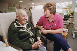 Elderly man and female clinic assistant sitting together laughing,