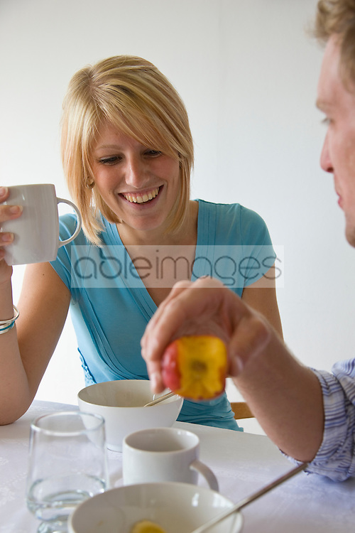 Young couple having breakfast talking and smiling