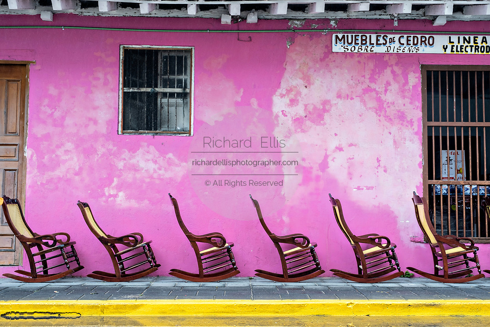 Traditional Poltrona style wooden rocking chairs on display against a pink wall in Tlacotalpan, Veracruz, Mexico. The tiny town is painted a riot of colors and home to legendary Mexican musician Agustín Lara.