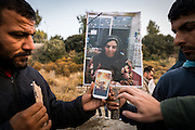 LESVOS, GREECE - NOV 26: Refugees show a photo of the burning body of the Kuridish woman who was killed when a gas cylinder exploded inside her tent in the Moria Detention Centre on Thursday night. Refugees and migrants gathered in the town of Mytilene to take part in a demonstration against the treatment of people inside the Moria camp.