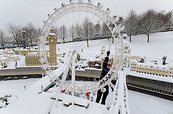© under license to London News Pictures. 21/12/2010. A snow covered Lego London at Miniland, Legoland Windsor this morning (21/12/2010) following further snowfall last night. Pictured is model maker Joel brushing snow from the London Eye. Photo credit should read: London News Pictures