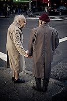 An elderly couple hold hands while waiting to cross the street in New York City, NY.