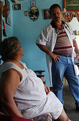 Roberto Hernandez is one of over 1000 Cuban doctors working in Venezuela as part of a government health program.  Hernandez, 38, has spent 2 months of a 2 year stint working in San Pablito, a poor community in Caracas.  Originally from Cien Fuegos, Hernandez has also worked in Angola and the Carribean, spending 2 years in each location.  Dr. Hernandez spends the mornings seeing patients in his home, which doubles as on office.  He spends the afternoons making house calls.  Here he is checking on Margarita Mendez, who has varicose ulcer's on her ankles.