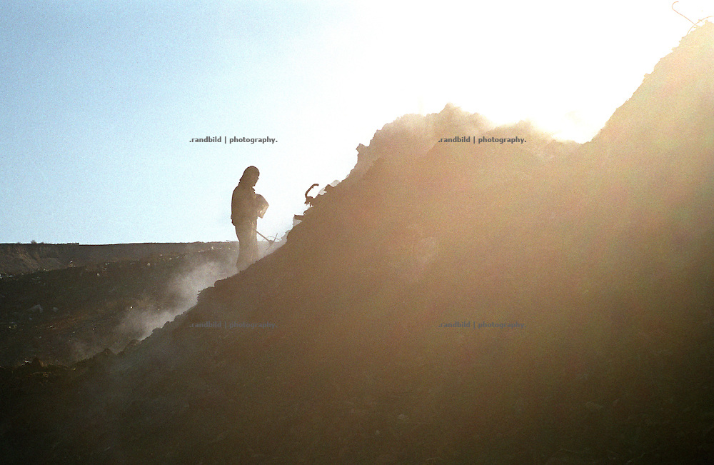 ARM, Armenien, Eriwan 10.12.2003, Ein mann sucht auf der Muellkippe der armenischen Hauptstadt Eriwan nach Verwertbarem. A junk colleter seaks for valuable waste at a smoking dump near Yerevan, Armenia.