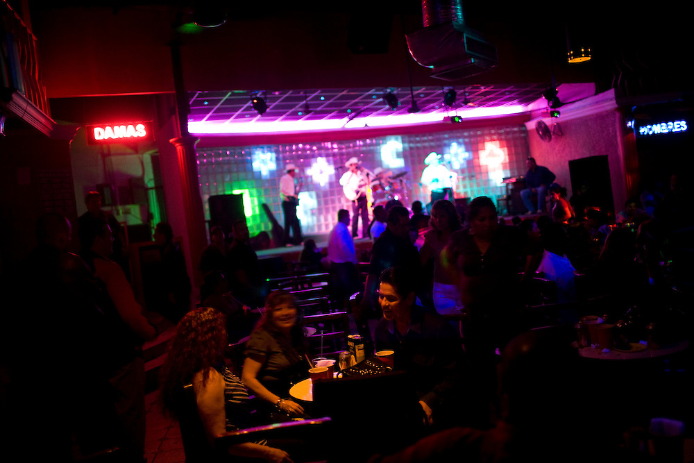 "People dance and drink and a nightclub while a group of Norteno musicians play music in downtown Culiacan.  Norteno music is famous for its ""corridos"", or ballads.  Many musicians compose corridos about drug lords that become part of popular culture.  This style of music is increasingly popular and is part of Mexico's emerging Narco culture."
