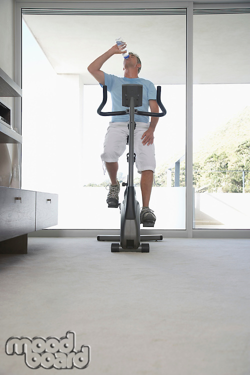 Mature man on exercise bike pedalling drinking bottle of water