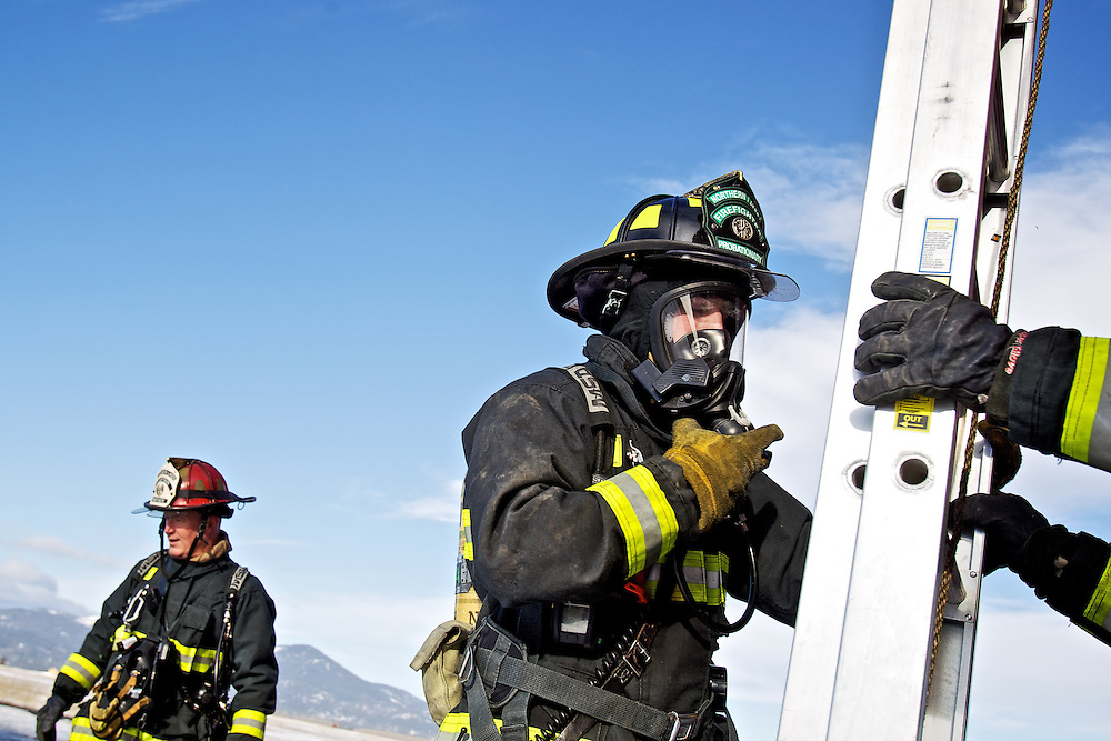 Northern Lakes firefighters Cody Moore helps set up a ladder before the start of a practice routine inside the fire department's training tower Wednesday, Jan. 25, 2012 at the Coeur d'Alene Airport in Hayden, Idaho.
