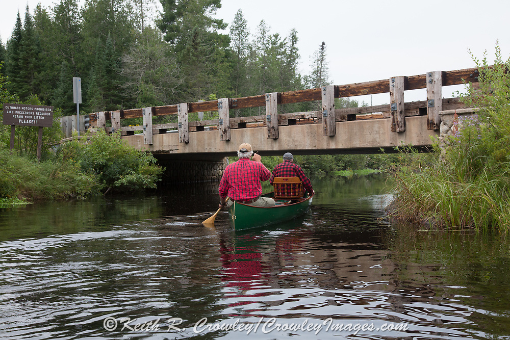 Brule River fishing guide Damian Wilmot (paddling) heads upstream with angler Matson Holbrook, under Stone's Bridge in a 1895 Lucius guide canoe Wilmot restored.