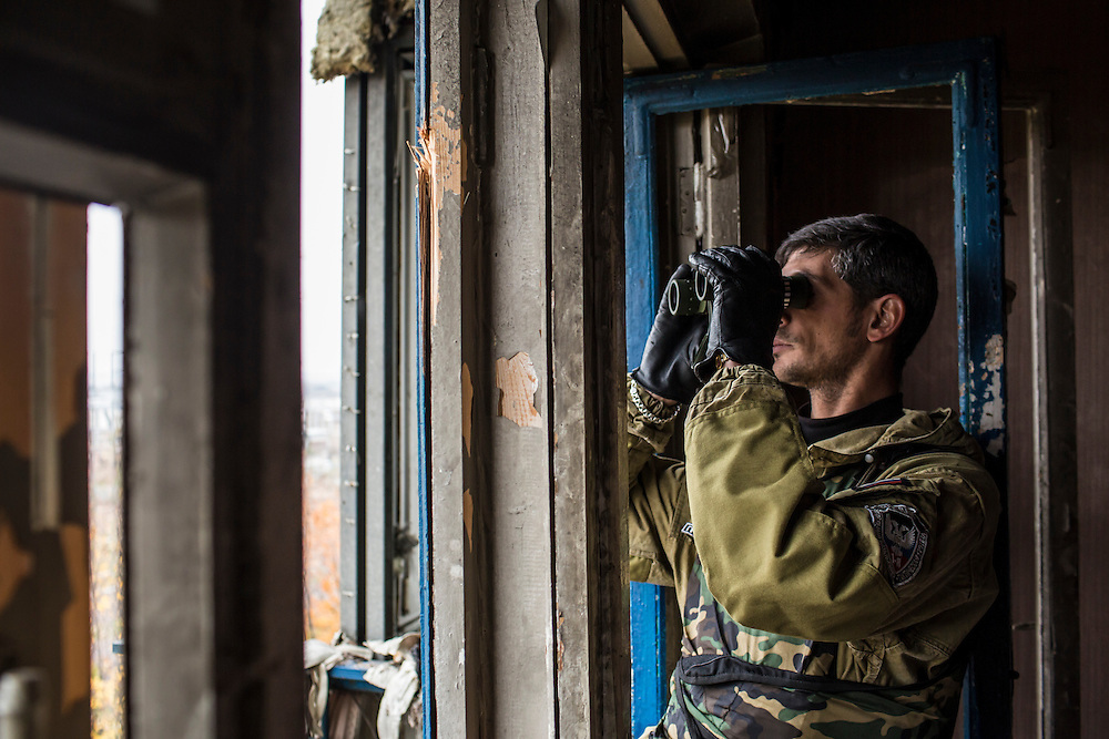 Pro-Russian rebel commander Mikhail Sergeevich Tolstikh, known as Givi, looks through binoculars in an apartment building where his forces can observe and coordinate fighting to gain control of the Donetsk airport on Friday, October 17, 2014 in Donetsk, Ukraine.