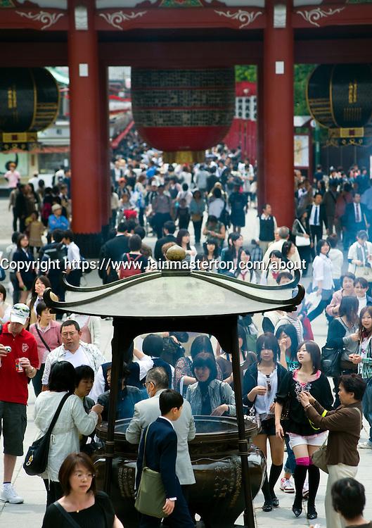 Crowds attending famous Senso Ji temple in Tokyo Japan