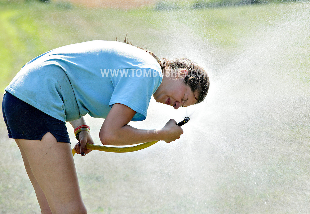 Becky Stap of Stap Family Dairy Farm in Pine Bush, N.Y., sprays herself with a hose after using the water to cool off a cow at the Orange County 4-H Showcase at Bergin Farm in Slate Hill, N.Y., on Thursday, July 18, 2013. Temperatures were in the mid-90s in the afternoon. (AP Photo/Times Herald-Record, Tom Bushey)
