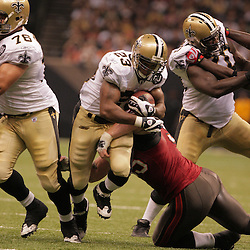 2008 September 7: New Orleans Saints running back Pierre Thomas (23) rushes as Tampa Bay Buccaneers defensive tackle Chris Hovan (95) tries to tackle him during their game at the Louisiana Superdome in New Orleans, LA.  The New Orleans Saints defeated the Tampa Bay Buccaneers 24-20.