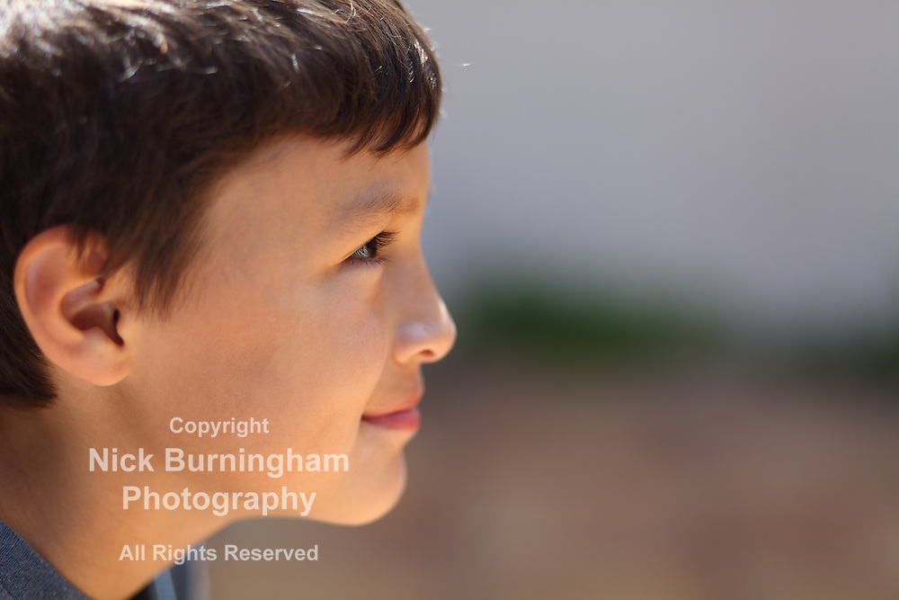 Profile of young boy looking to right into copy space near sunset - very shallow depth of field