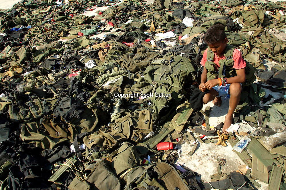 A young boy looks through discarded uniforms of the paramilitary group Bloque Norte, or Northern Block, after a disarmament ceremony in La Mesa in northern Colombia on March 10, 2006. An estimated 24,000 paramilitary members have turned in their weapons as part of a government negotiated peace deal. But some are skeptical if the government plan will really work and if the paramilitary members will be successful in their transformation to civilian life. (Photo/Scott Dalton)