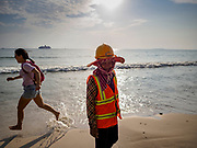 "12 FEBRUARY 2019 - SIHANOUKVILLE, CAMBODIA: A Cambodian construction worker walks past a Chinese tourist running down the beach near the Blue Bay resort development. Blue Bay is a Chinese casino and resort being built in Sihanoukville. There are about 50 Chinese casinos and resort hotels either open or under construction in Sihanoukville. The casinos are changing the city, once a sleepy port on Southeast Asia's ""backpacker trail"" into a booming city. The change is coming with a cost though. Many Cambodian residents of Sihanoukville  have lost their homes to make way for the casinos and the jobs are going to Chinese workers, brought in to build casinos and work in the casinos.       PHOTO BY JACK KURTZ"