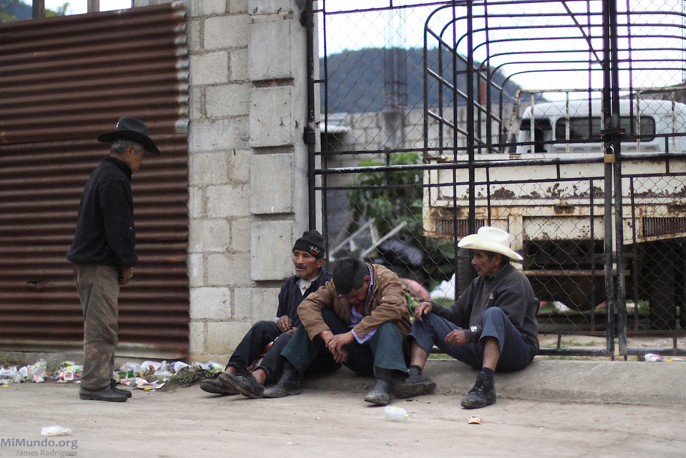 Drunk men sit on a sidewalk. Concepción Huista, Huehuetenango, Guatemala. February 4, 2013.
