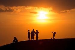 © Licensed to London News Pictures. 25/07/2018. LONDON, UK.  People watch the sunset at Northala Fields in Northolt, West London, after another day when temperatures reached 30C.  The forecast is for temperatures to increase further to 35C by the end of the week.  Photo credit: Stephen Chung/LNP