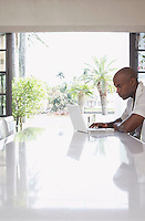 Man using laptop on dining table side view