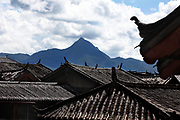 A view across rooftops to mountains west of Lijiang,Yunnan, China; September, 2013.