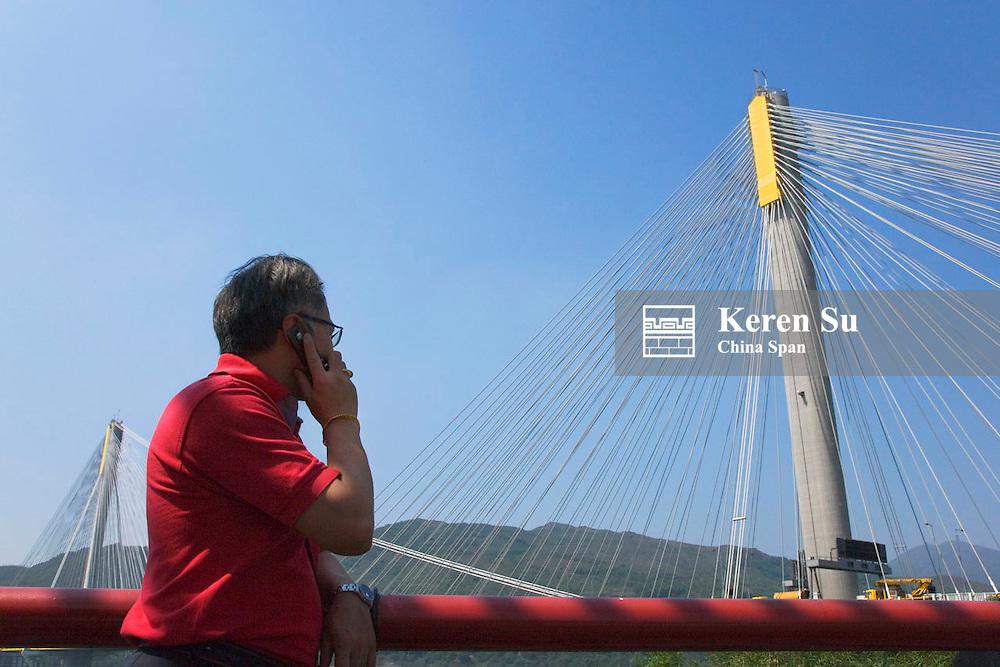 Man on cellular phone with Tsing Ma Bridge, Hong Kong, China
