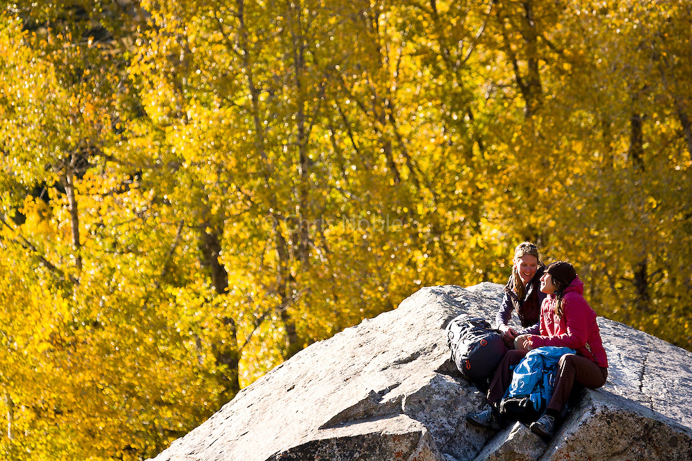 Trindl Nebeker and Ashley Gish sit and talk amid autumn colors while hiking in Utah's Wasatch Mountains.