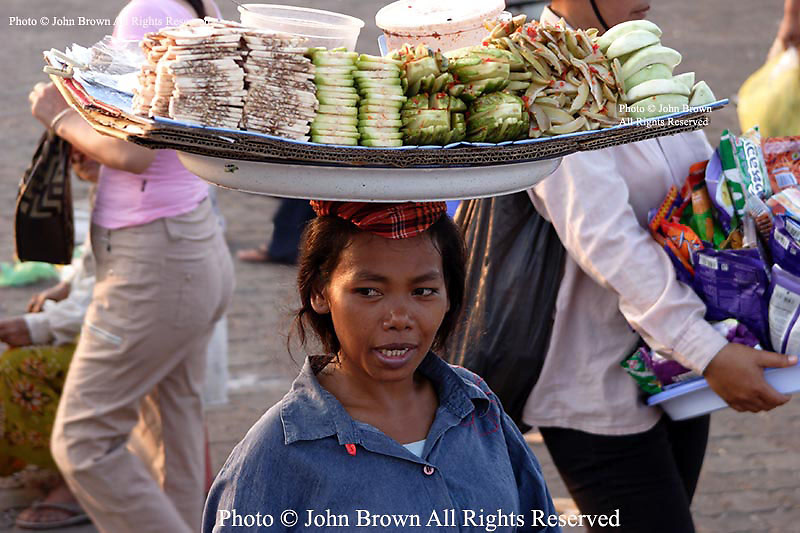 A woman who works as a food vendor balances a tray on her head near the banks of the Mekong River in Phnom Penh, Cambodia.