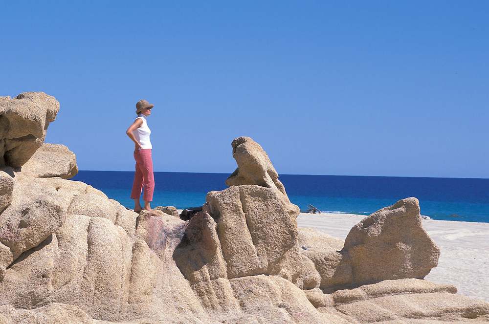 Woman with pink pants and hat,standing on cliffs at seashore,Los cabos,Baja California, Mexico