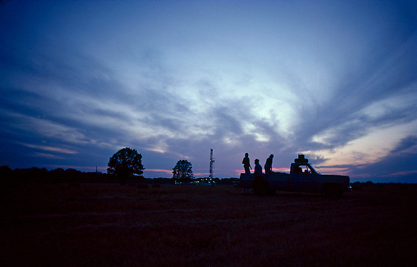 Stock photo of the silhouette of men in the back of their pickup with an oil and gas drilling rig in the background at sunset in Texas