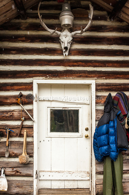 A pistol, down jacket and antlers hang around a door on a log cabin.
