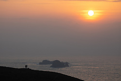 © Licensed to London News Pictures. 24/03/2020. Wadebridge, UK. Walkers watch the sunset from Trevose head, Cornwall, the evening after British Prime Minister Boris Johnson ordered a lockdown to slow the spread of Coronavirus (COVID-19) across the country. Photo credit : Tom Nicholson/LNP