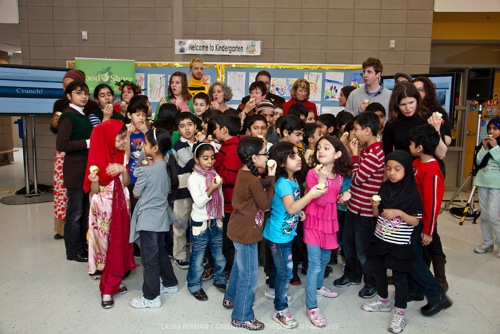 Thorncliffe Park students and Hon. Carol Mitchell, Hon. Laurel Broten, Don Werden of Norfolk Fruit Growers' Association, TDSB Trustee Howard Goodman, Sharon Brodovsky from the Heart and Stroke Foundation of Ontario, School Principal Kevin Battaglia, and Meredith Hayes at FoodShare's Great Big Crunch, March 10, 2011 at Thorncliffe Park Public School.