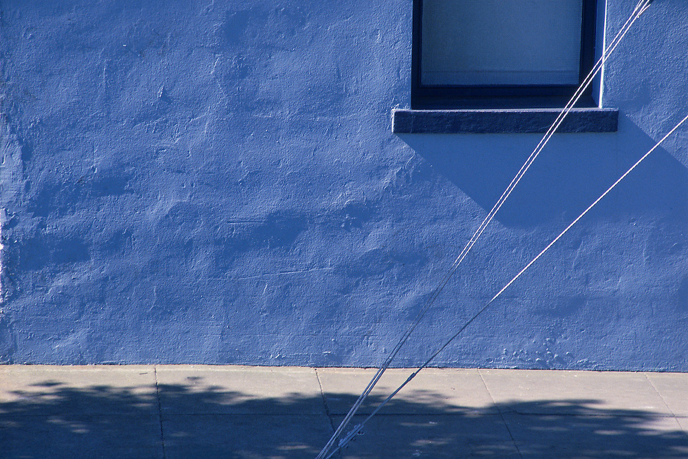 A blue shadow spills over sidewalk that butts against a blue stucco wall. Metal guide wires cut through the frame on a diagonal.