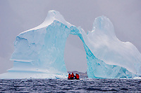 A zodiac exploring an arch sculpted tabular iceberg grounded in Pleneau Bay near Port Charcot, Antarctica.