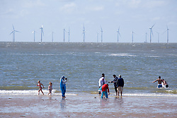 People on New Brighton beach Liverpool Bay; with the Burbo Bank offshore wind farm which comprises 25 wind turbines in the background, The wind farm is capable of generating up to 90MW (megawatts) of clean; environmentally sustainable electricity; enough power for approximately 80;000 homes,