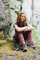 Portrait of a late 20's woman wearing rock climbing gear sitting below rock cliffs