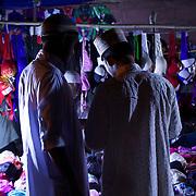 Two after-dark shoppers are buying lingerie at a stall in Old Delhi.