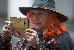 © Licensed to London News Pictures. 22/01/2018. London, UK. A member of the campaign group LAW (Labour Against the Witch-hunt) takes a photograph while wearing a witches hat, outside Labour Party headquarters ahead of an NEC (National Executive Committee) meeting. The group are campaigning against the suspension of party members over alleged antisemitism. Photo credit: Ben Cawthra/LNP