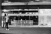 Brussels Belgium 2017 september 7. ontruiming Noordstation door de federale politie. Alle asielzoekers en transitmigranten die op Station Noord overnachten zijn vanochtend door de politie omsingeld en stuk voor stuk gecontroleerd.Hierna werd een gedeelte afgevoerd. Man wacht op bus terwijl fouillering doorgaat in achtergrond.