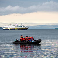 Guests on an inflatable boat, or zodiac, cruise at Jones Island Marine State Park in the San Juan Islands of Washington State with the National Geographic Venture ship in the background.