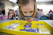 """Lila Kelly, 5, of south Des Moines, inspects snowflakes with a magnifying glass Tuesday, Dec. 23, 2014, during a """"Frozen"""" party, themed on the movie, at the Franklin Avenue Library in Des Moines."""
