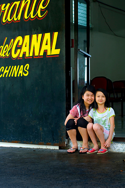 Chinese sisters pose in front of their mother's Chinese restaurant on the Panama Canal, Panama.