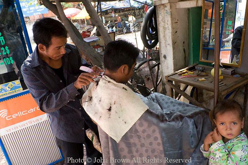 A street barber concentrates on his work as a young girl is standing nearby at a street barbershop in Phnom Penh, Cambodia.