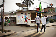 Two men walking past an entertainment center selling food and drinks in downtown Freetown, Sierra Leone