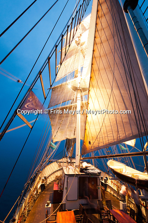 Ireland, July 2013. Sailing through the Blue hour. It is the first time that Tallship Thalassa, a barquentine sailing vessel with 3 masts, sails from Belfast to Galway along the Irish coastline. While a full-rigged ship is square-rigged on all three masts, and the barque is square-rigged on the foremast and main, the barquentine extends the principle by making only the foremast square-rigged. The advantages of a smaller crew, good performance before the wind and the ability to sail relatively close to the wind while carrying plenty of cargo made it a popular rig at the end of the 19th century. Photo by Frits Meyst/Adventure4ver.com