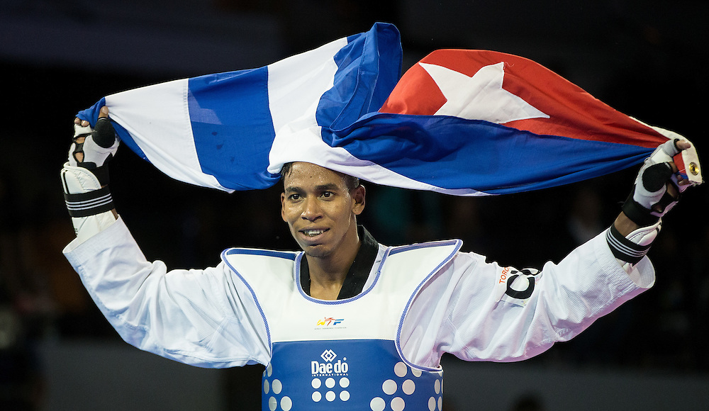Jose Cobas (R) of Cuba celebrates his victory over Moises Hernandez of the Dominican Republic during their gold medal contest in the men's taekwondo -80 kg division at the 2015 Pan American Games in Toronto, Canada, July 21,  2015.  AFP PHOTO/GEOFF ROBINS