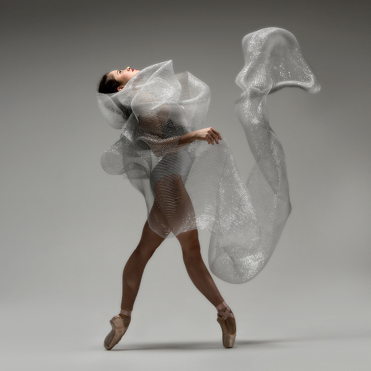 Classical ballet ballerina, Ana Maria Delmar, wrapped in silver fabric. Taken in the photo studio on a grey background. Photograph taken in New York City by photographer Rachel Neville.
