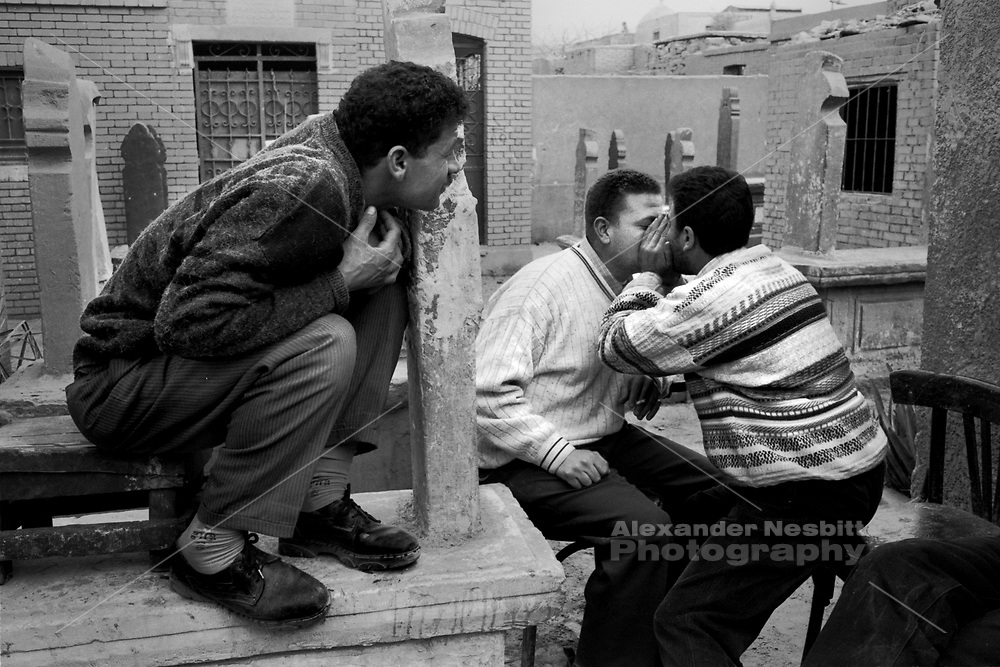 "Cairo, Egypt, The City of the Dead, 2000 - Undertakers and laborers ""shotgun"".  Drug use is much more common across the cememtery than in Egyptian society in general."