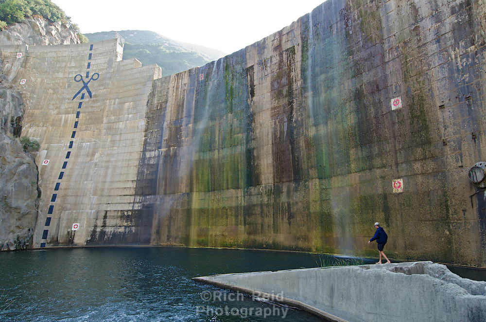 Paul Jenkin walking on a defunct fish ladder below scissors and cut marks painted on the obsolete Matilija Dam in Los Padres National Forest near Ojai, California.