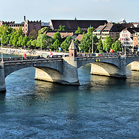 Middle Bridge Over Rhine in Basel, Switzerland <br /> In 1226, the stone and wood Middle Bridge was built over the Rhine River to connect the main section of Basel called Grossbasel with the Kleinbasel or right bank (shown).  In the middle is the K&auml;ppelijoch chapel where unfaithful women prayed before being bound, weighted and thrown into the water below.  In 1905, the Mittlere Br&uuml;cke was reconstructed.